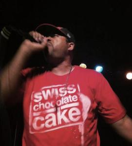 Mr. Complex  performing at album release wearing Swiss Chocolate Cake t-shirt